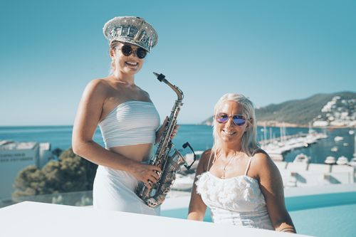 Ibiza wedding pianist and saxophone duo posing for a photo with white grand piano on top of Aguas de Ibiza rooftop.