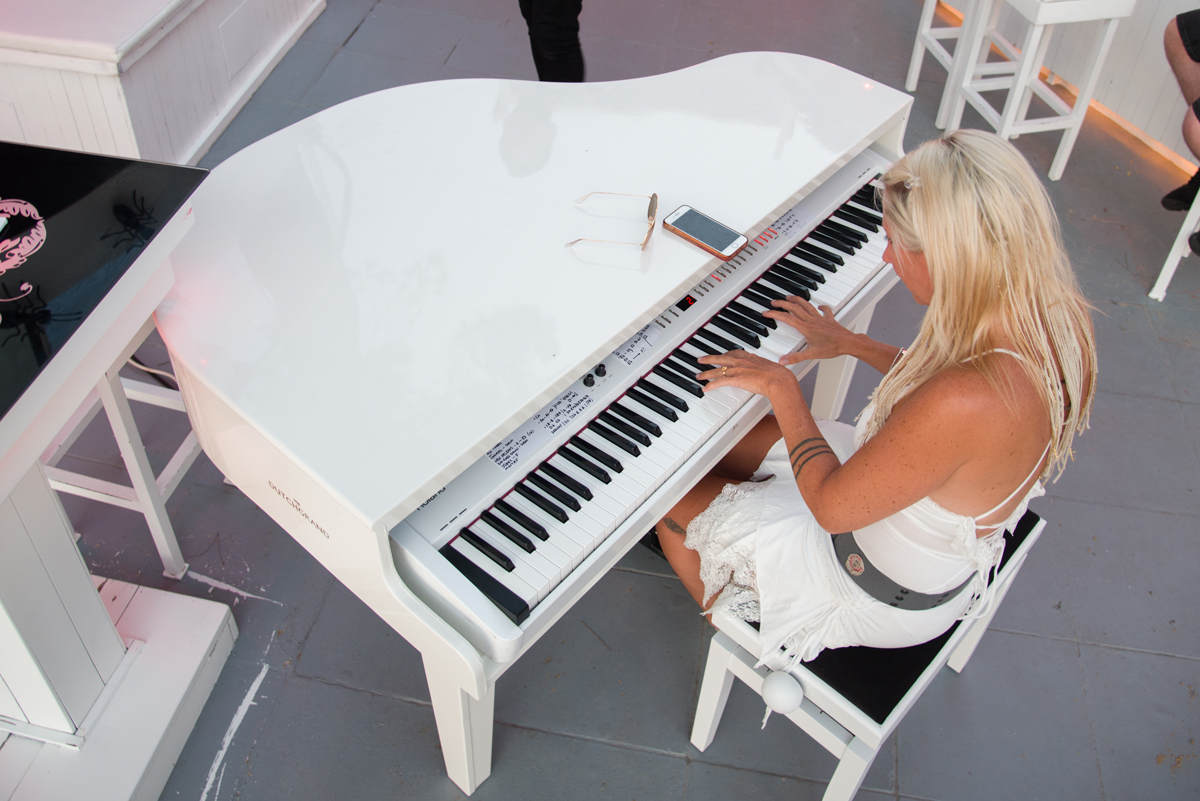 Unique white grand piano shell for hire in Ibiza. Photo taken from above, looking down on the piano.